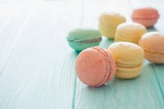 Assortment of macarons on blue wood background. Assorment of colorful homemade  macarons on blue wood background. Close up. Selective focus Stock Photos