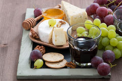Assorted appetizers to wine - cheeses, fresh grapes, crackers Stock Photos