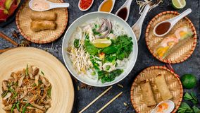 Assorted asian dinner, vietnamese food. Pho ga, pho bo, noodles, spring rolls. Top view stock photos