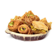 Assorted baklava pastries. Closeup of an earthenware plate with some different baklava pastries, on a white background stock images