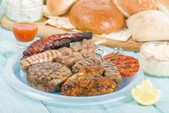 Assorted Barbequed Meat. BBQ - Assorted barbequed meat and bread on a blue background. Served with coleslaw, yoghurt and cucumber dip and chili sauce. Outdoors royalty free stock images