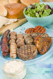 Assorted Barbequed Meat. BBQ - Assorted barbequed meat and bread on a blue background. Served with coleslaw, yoghurt and cucumber dip and chili sauce. Outdoors royalty free stock photo