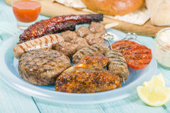 Assorted Barbequed Meat. BBQ - Assorted barbequed meat and bread on a blue background. Served with coleslaw, yoghurt and cucumber dip and chili sauce. Outdoors stock image