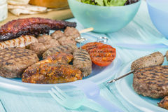 Assorted Barbequed Meat. BBQ - Assorted barbequed meat and bread on a blue background. Served with coleslaw, yoghurt and cucumber dip and chili sauce. Outdoors royalty free stock photography