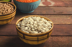 Assorted beans in bowls with red lentil, chick-pea and kidney bean on wooden background. Royalty Free Stock Images