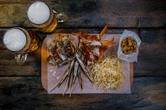 Assorted beer snacks with beer mugs stock image