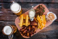 Assorted beer snacks with beer mugs royalty free stock photo