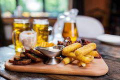 Assorted beer snacks with beer mugs royalty free stock image