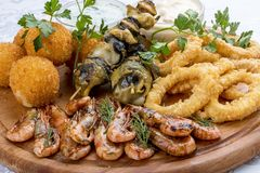 Assorted beer snacks. Cheese balls, mussels grill, shrimp, squid rings royalty free stock image