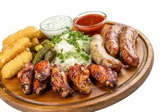 Assorted beer snacks. Cheese sticks, pickled cucumbers, grilled sausages, sauerkraut, chicken wings royalty free stock photography