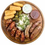 Assorted beer snacks. Cheese sticks, pickled cucumbers, grilled sausages, sauerkraut, chicken wings stock photos