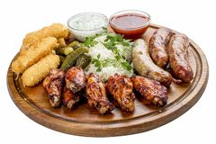 Assorted beer snacks. Cheese sticks, pickled cucumbers, grilled sausages, sauerkraut, chicken wings stock image