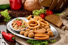 Assorted beer snacks: onion rings, cheese balls, chips etc on a iron tray on a dark wooden background among vegetables. royalty free stock photos
