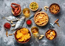 Assorted beer snacks. Selection of beer and snacks.Chips, fish, beer sausages on the table royalty free stock photo