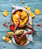 Assorted beer snacks. Selection of beer and snacks.Chips, fish, beer sausages on the table stock photography