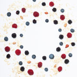 Assorted berries and oatmeal. Set for a healthy breakfast as a circle frame. Raspberries, blueberries, blackberries, peanuts and oatmeal Stock Photo
