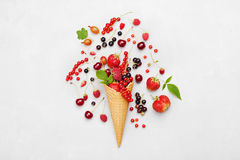 Assorted berries in waffle cone on light background from above. Dietary and healthy dessert. Flat lay styling. Royalty Free Stock Image