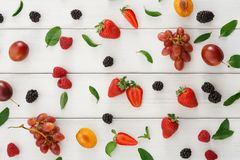 Assorted berries on white wooden table top view. Mix of organic berries background. Pattern of fresh strawberries, plums, raspberries, grapes, blueberries and Royalty Free Stock Photography