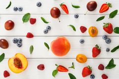 Assorted berries on white wooden table top view. Mix of organic berries background. Pattern of fresh strawberries, plums, raspberries, peaches, blueberries and Stock Photo