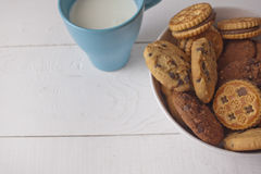 Assorted biscuits in bowl with cup milk. Assorted biscuits in bowl with blue cup milk royalty free stock photo