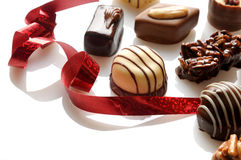 Assorted bonbons with red ribbon on a white table close-up Royalty Free Stock Photography