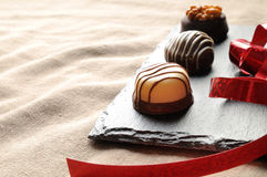 Assorted bonbons on a slate plate with red ribbon close up Royalty Free Stock Images