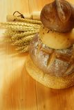 Assorted bread. On wooden table with raw wheat and baking roller background Stock Photo