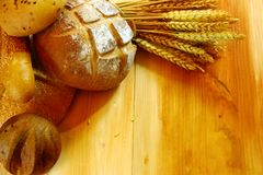 Assorted bread background. Assorted bread on wooden table with raw wheat Stock Image