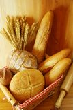 Assorted bread on basket. With raw wheat and wood background Royalty Free Stock Photography