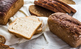 Assorted bread, slices of rye bread on linen tablecloths, wooden Royalty Free Stock Photos