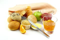 Assorted Breakfast Bread. Accompanied with strawberry jam, orange marmalade ,butter , apple and orange on white back ground Stock Image