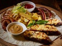 Assorted briet Würste, gegrillte Kartoffeln, Soße Adjika, Senf-Soße Lizenzfreie Stockbilder