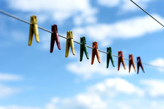 Assorted Bright Plastic Clothes Pegs on a Washing Line. An assortment of brightly colored washing pegs and clothespins on a outdoor washing line with bright blue Stock Photo