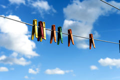 Assorted Bright Plastic Clothes Pegs on a Washing Line. An assortment of brightly colored washing pegs and clothespins on a outdoor washing line with bright blue Stock Photos