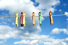 Assorted Bright Plastic Clothes Pegs on a Washing Line. An assortment of brightly colored washing pegs and clothespins on a outdoor washing line with bright blue Royalty Free Stock Photo