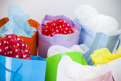 Assorted brightly coloured paper shopping bags. Assorted brightly coloured paper gift bags on a white background Royalty Free Stock Photo