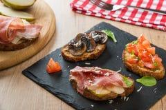 Assorted bruschettas on slate plate Royalty Free Stock Photos