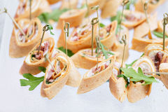 Assorted canape with cheese, meat, rolls, tortilla and fruit salad. Food to accompany the drinks. the buffet at the Royalty Free Stock Photos
