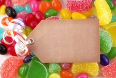 Assorted Candies with Tag, Copy Space. A bright colored assorted candy background with blank brown tag for copy space Royalty Free Stock Photos