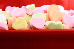 Assorted Candy Hearts in Red Candy Bowl. Closeup of assorted pastel candy hearts for Valentines Day in a red ceramic candy bowl. Shallow depth of field. The stock photos