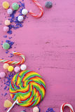 Assorted candy and lollipop on pink wood table. Stock Photos