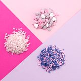 Assorted candy sprinkles piles. On pastel colored background Stock Photos