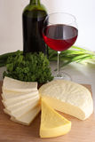 Assorted cheese. On wood board, wine bottle and wineglass Royalty Free Stock Photography