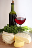 Assorted cheese. On wood board, wine bottle and wineglass Royalty Free Stock Photos