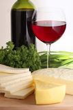 Assorted cheese. On wood board, wine bottle and wineglass Stock Photo