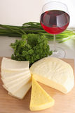 Assorted cheese. On wood board, wineglass and greens Stock Images