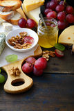 Assorted of Cheese with grapes, honey bread and walnuts on cutting board Stock Photo