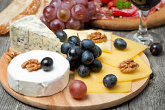 Assorted cheese, grapes, wine and sausages Stock Image