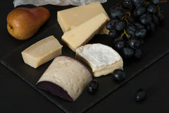 Assorted Cheese On Slate Stone. Grapes, Pears Royalty Free Stock Images