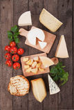 Assorted cheese on wooden platter. Rich and healthy breakfast or snack food Royalty Free Stock Photo